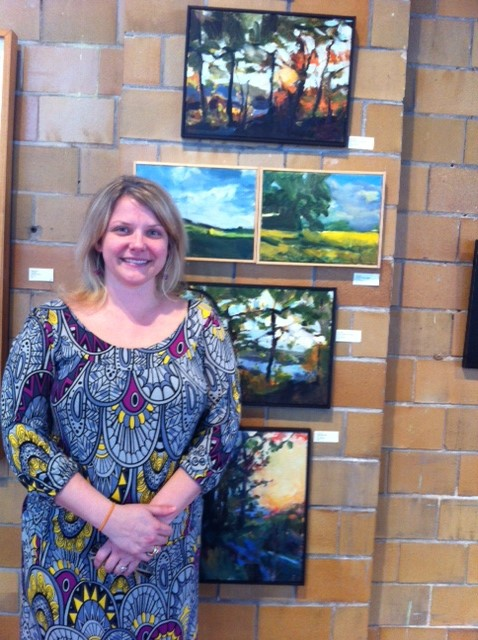 Cate Yellig at Covington Arts Cemter in front of pictures by Kim Flora