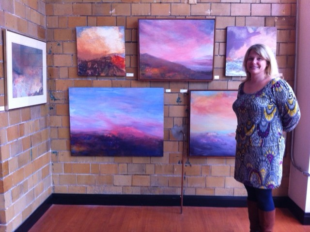 Cate Yellig at Covington Arts Center in front of pictures by Valerie Shesko